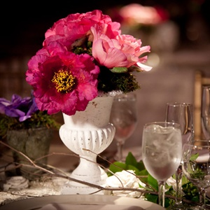 Rustic white urns held fresh fuchsia and lavender blooms.