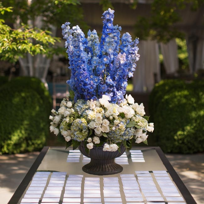 The simple escort cards were displayed on a glass table with a large blue-and-white floral arrangement.