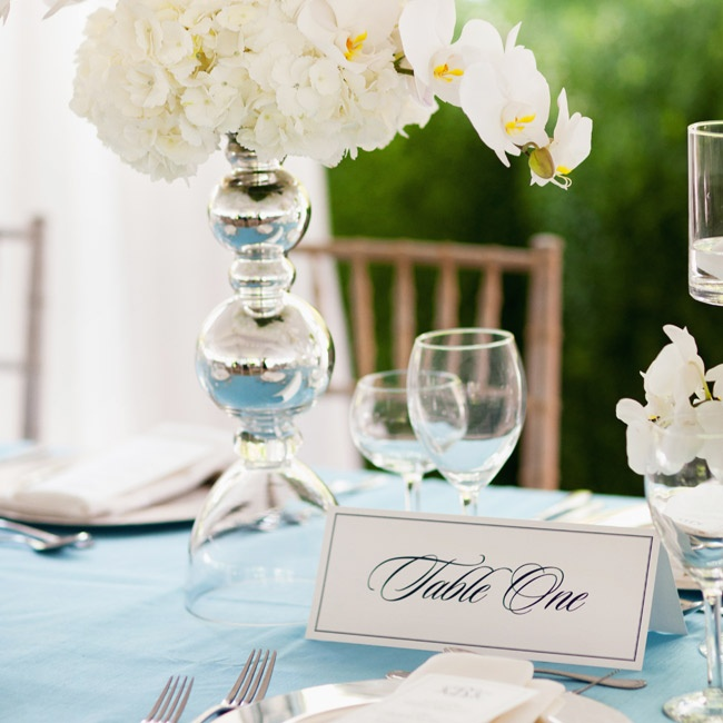 White hydrangeas and orchids filled vases on the reception tables. Script table numbers matched the chic look.