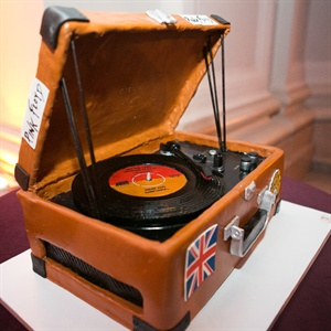 "Jed's gluten-free cake was designed to look like a record player in a suitcase. It included ""stickers"" from his favorite bands on the outside for a personal touch."