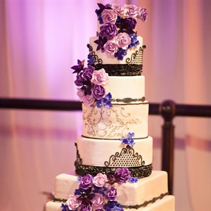 The ornate, eight-tiered white-fondant cake was adorned with purple sugar and gum-paste flowers, along with elegant scrolling.