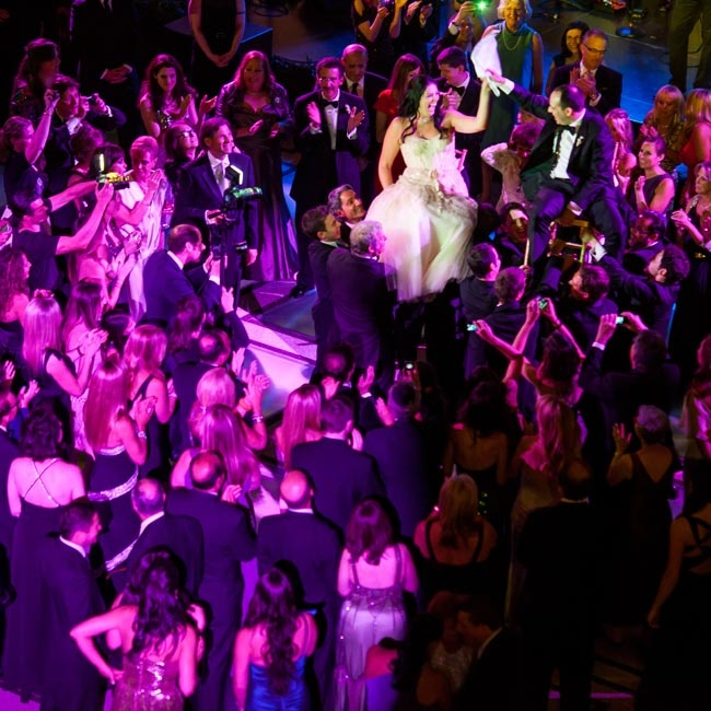 At the reception, the couple was hoisted into the air on chairs for the hora.