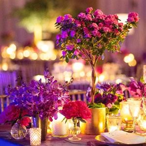 Mini magenta azalea topiaries and smaller arrangements of peonies and cabbage roses topped reception tables.