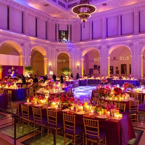 Deep-purple uplighting, rich raw silk linens and well-placed candlelight set a romantic scene.