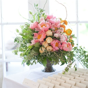 A large urn, overflowing with peonies, roses and ranunculus, topped the escort card table.