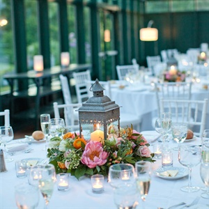 Rustic lanterns were surrounded by lush florals and greenery on the white-clothed reception tables.