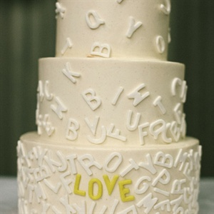 "The buttercream cake was topped with white cascading alphabet letters; yellow ones spelled out ""love."""