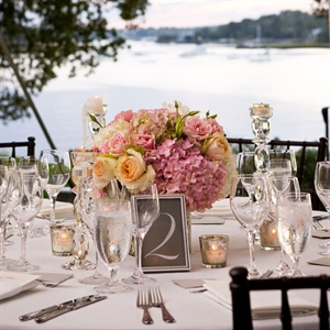 Rounded arrangements of pink and peach roses topped the reception tables.
