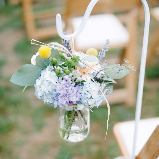 Mason jars filled with fresh flowers hung from white shepherd's hooks.