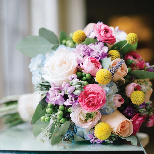 Emily carried a bright bunch of billy balls, ranunculus, stock, roses and berries.