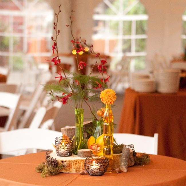 Small vases holding orange and red Mokara orchids, dahlias and ferns rested on wood stands.