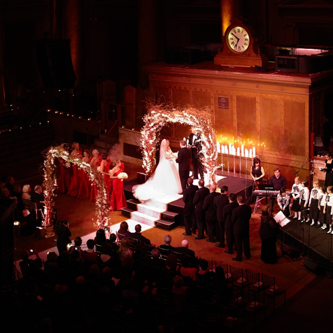 The entire evening took place in the grand space of the Capitale ballroom, which features dramatic high ceilings and old-world charm. The archways lining the aisle were made from curly willow branches and adorned with hanging crystals and white dendrobuim orchids. To add a final touch, the couple had a custom runner made from Original Runner Compan ...