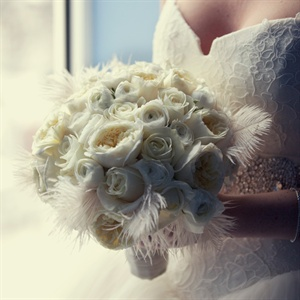 White feathers added a glamourous touch to her otherwise all-white bridal bouquet.