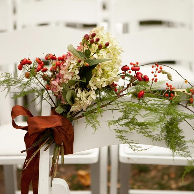 To honor Joe's dad, who had passed away years earlier, the couple saved a seat for him at the ceremony and decorated it with berries, hydrangeas and ferns.