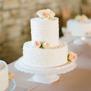 Several smaller cakes had buttercream frosting and were topped with fresh blush roses.