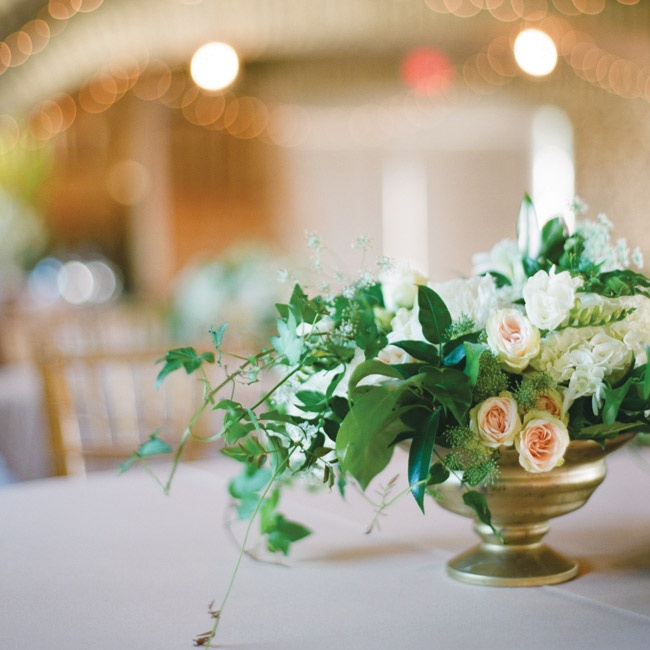 Low, bronzed vases overflowed with greenery and soft-hued roses.