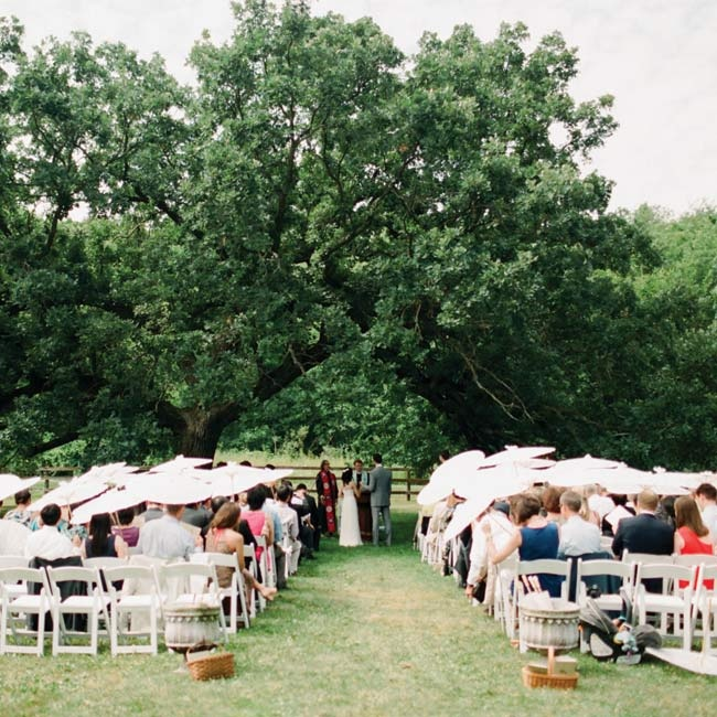 Guests shielded themselves from the sun with parasols as the couple exchanged vows under the twisted branches of a giant oak tree.