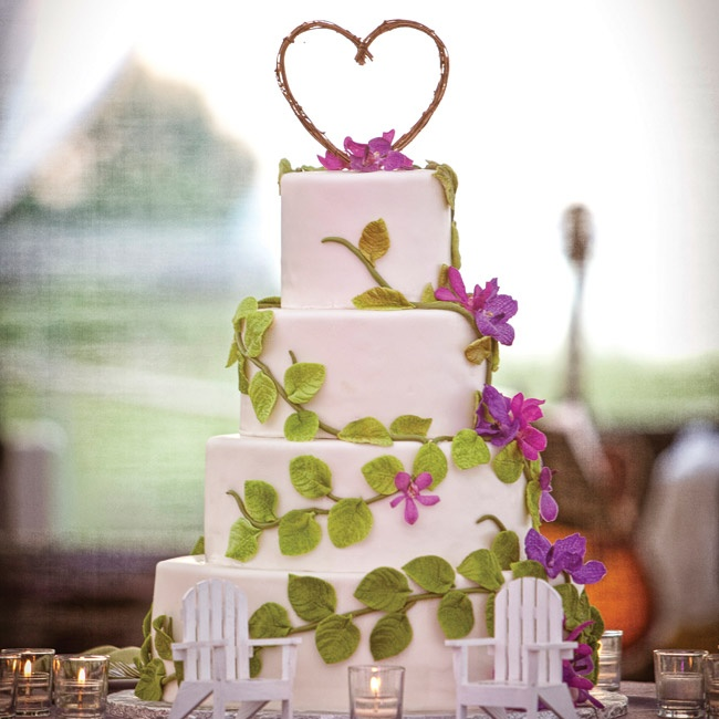 Green-fondant leaves and vines and fresh purple flowers wrapped around the four-tiered cake.