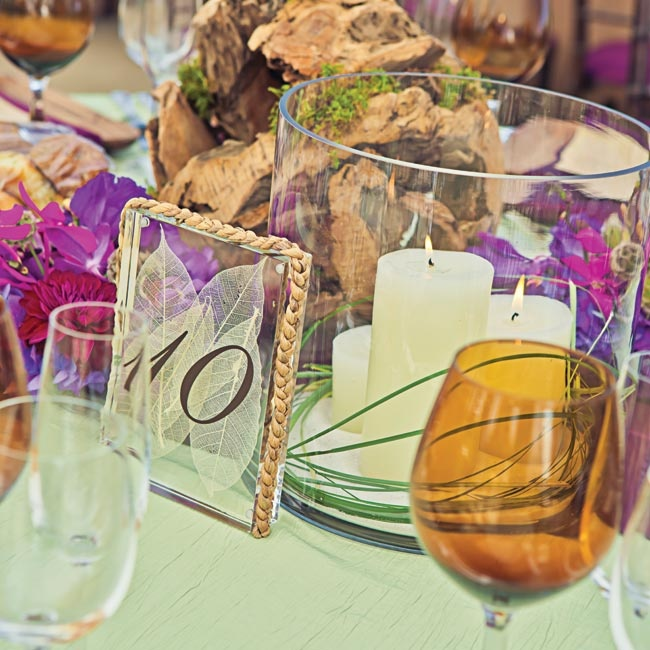 Glass table numbers, votives and rustic wooden accents decorated the tables.