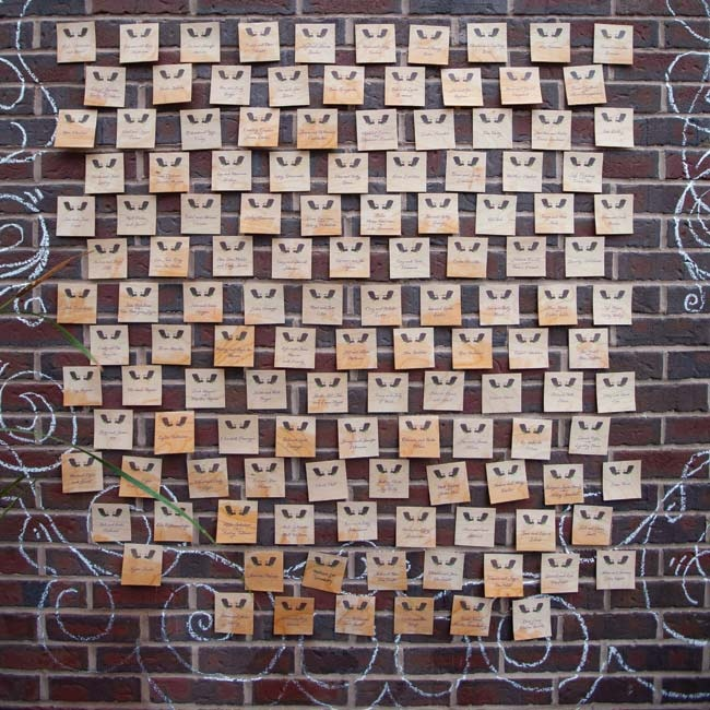 The thin wooden escort cards were arranged and displayed on a brick wall.