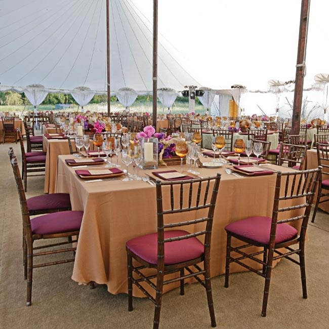 Soft-orange linens topped tables. Deep-fuchsia seat covers and napkins added a pop of color to the setting.