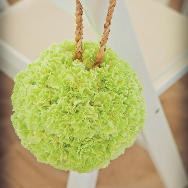 Green carnation pomanders hung from ceremony chairs.