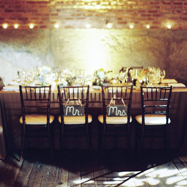 "Megan and Mike's reception chairs were decorated with fun ""Mr."" and ""Mrs."" signs."