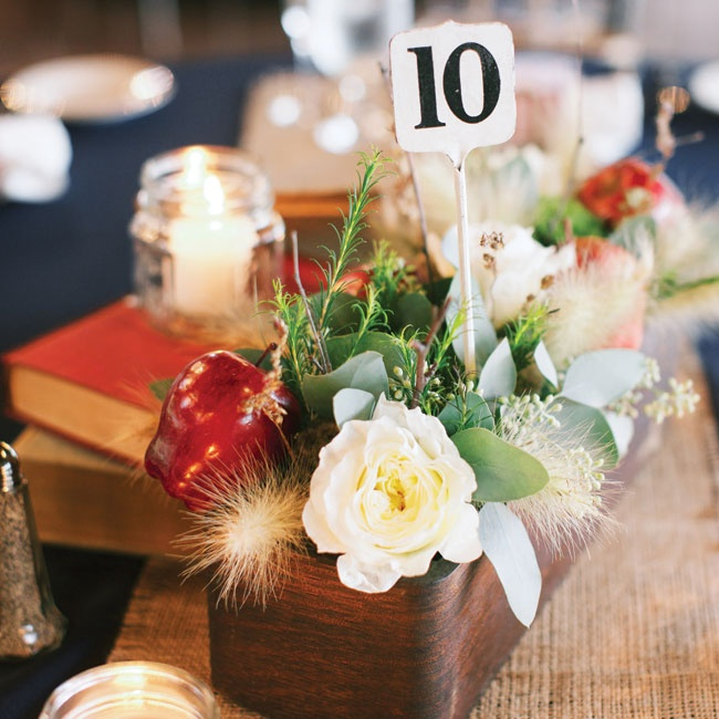 Interesting arrangements of apples, flowers, greens and wheat topped the reception tables, along with burlap runners and table numbers.