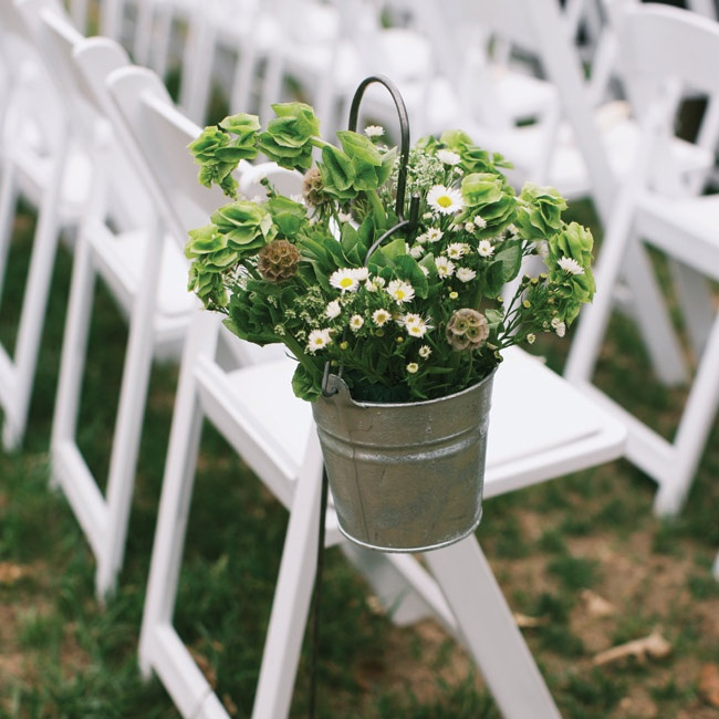 Galvanized buckets filled with bells of Ireland, Queen Anne's lace and Monte Casino asters hung from shepherd's hooks along the aisle.