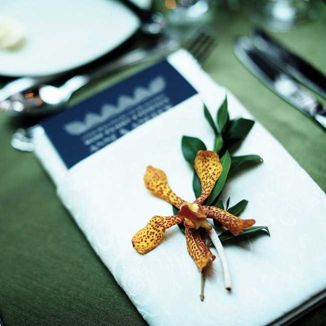 An orange speckled Mokara orchid and a sprig of myrtle rested at each guest's seat.