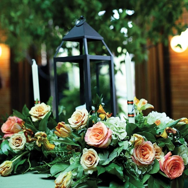 Rustic lanterns were surrounded by lush gatherings of flowers, greens and candles.