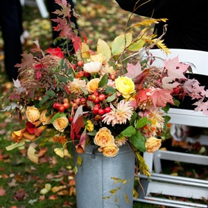 Metal pails at the entrance to the ceremony were filled with yellow and orange flowers and autumn leaves.