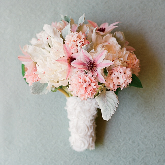 Flaunt your girly style front and center. This romantic and ethereal arrangement blends lamb's ear, hyacinths, clematis vine and full-bloom peonies in a soft palette of blush, pink and gray. For an extra-feminine flourish, a rosette-adorned wrap ties everything together.