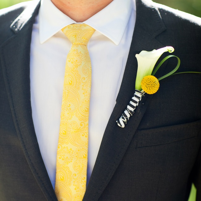 The calla lily boutonnieres were paired with yellow billy balls and wrapped in black-and-white-striped ribbon.