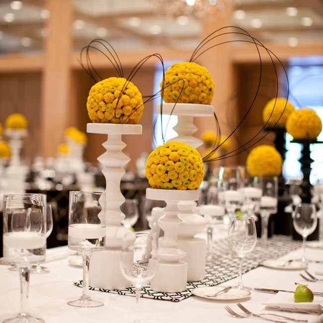 Yellow button-mum pomander centerpieces sat atop white and black pillars. The displays added a bold punch of color to the black-and-white table runners.