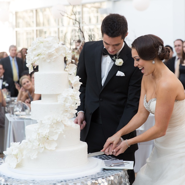 This white-fondant cake has tiers separated by three-inch spacers finished in textured, silver-painted fondant. The tiers are decorated with handmade white sugar orchids and piped embroidery painted in silver.