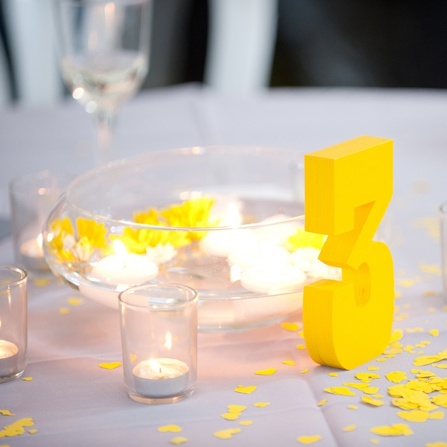 Brittany and John wanted something simple and low so their guests could talk, so they took a DIY approach and used floating blooms in glass bowls. Tea lights and bright yellow table numbers finished the look.