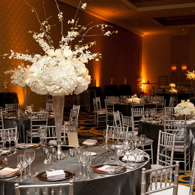 Reception tables were topped with silver linens and tall white arrangements of orchids, hydrangeas and roses.