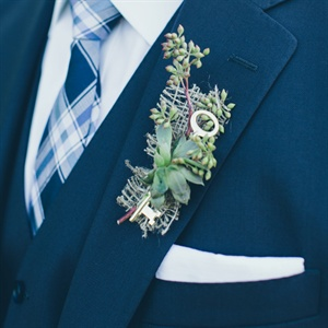 The groom wore a three-piece Tom James suit with a Banana Republic tie. The boutonniere was a single succulent accented with burlap and a skeleton key.