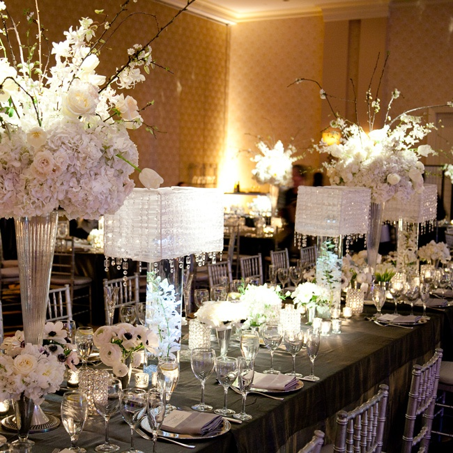 The florist helped the couple design the room layout with the head table as the focal point. They used the lampshades to add a modern twist and create different heights on the table.