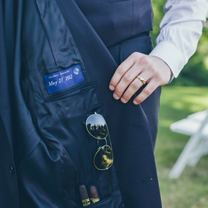 "A label inside the groom's custom Tom James suit read ""Exclusively Made For May 27, 2012."" He accessorized with a family heirloom wedding band, his favorite aviators for the sunny day and of course, celebratory cigars."