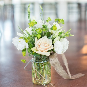 Mason jars filled with fresh picked garden flowers with a touch of burlap lined the aisle during the ceremony. The arrangements were moved to high-top tables for the reception.