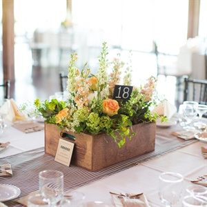 Handmade garden boxes, filled with an assortment of light garden flowers and mini succulents, made for the perfect low centerpiece. Small sticks painted with chalkboard paint showed the table numbers, and black ticking fabric runners pulled it all together.
