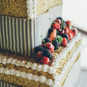 The three-tiered Rice Krispie cake was garnished with white icing and fresh berries, and accented with ticking fabric.