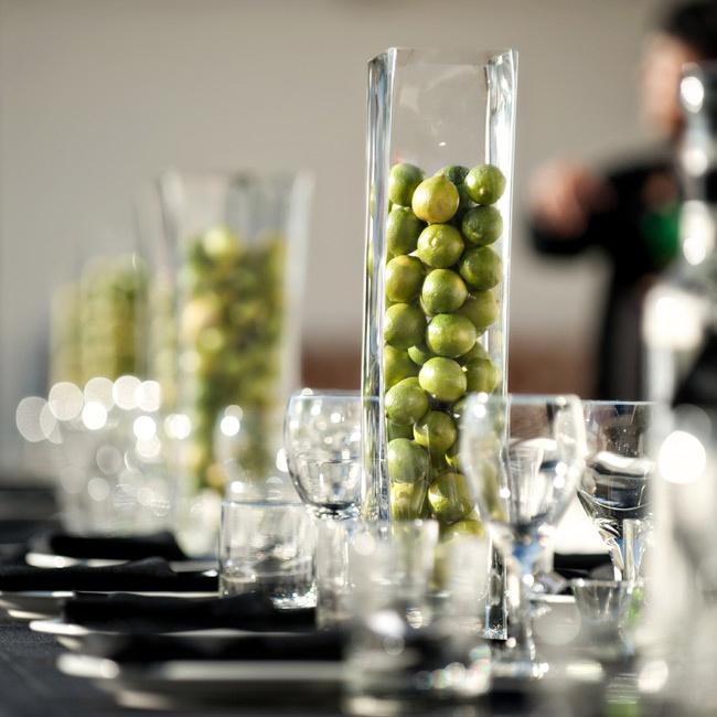 The reception tables held arrangements of tall vases filled with limes atop black linens.