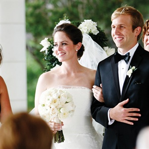 Jenny wore a frothy ivory gown that had three types of Chantilly lace. During the reception, she traded her white sash for a black one.