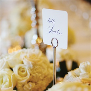 Votive candles and short centerpieces of ivory, white and cream flowers filled the space between the larger candelabra centerpieces and the table numbers.