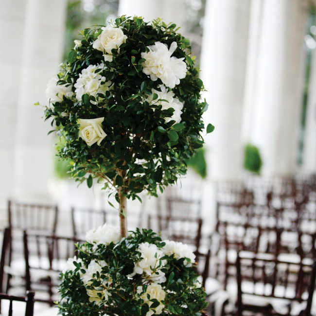 An ivory runner and large topiaries with roses were the only decorations the couple used at the ceremony.