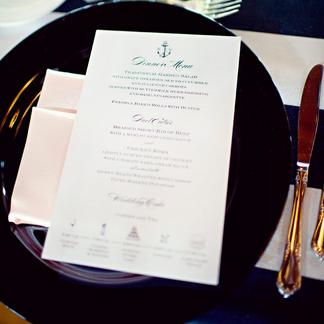 "As a nod to the nautical theme, the menu cards had the couple's signature anchor logo. The cards rested perfectly on a ""sea"" of shiny black chargers."