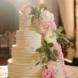 A vine of fresh flowers and a ruffled finish accented the simple four-tiered buttercream cake.